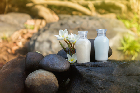 copy sapce: Mini set of bubble bath shower gel liquid with flowers and pebble on waterfall rock  with natural water relaxing feeling background and copy sapce Stock Photo