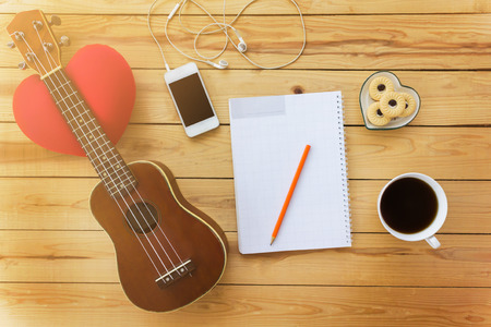 noe: Blank note book and pencil with coffee,cookie, mobile and ukulele in vintage style on jointed wooden background