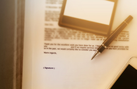 extol: Blurred business letter document with pen and blank area for text signature, job well done, admire letter