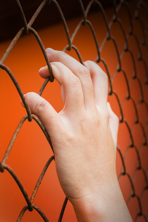 confine: Women hand catching iron bar on orange background, imprison feeling Stock Photo