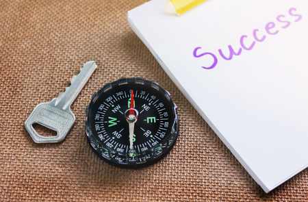 imply: compass with key and blurred text success on paper note, business concept Stock Photo