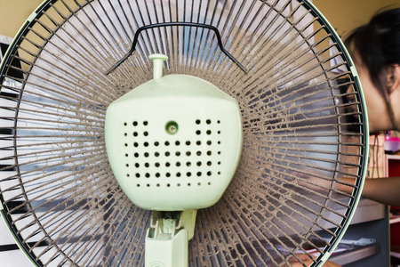 unclean: Dusty or unclean portable fan with blurred girl working at table Stock Photo