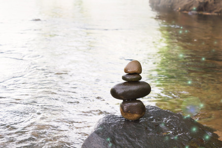 equivalence: Superimposed waterfall pebble rock arranged on big stone at waterfall background with copy space