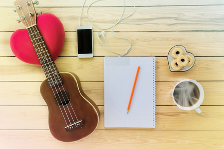 noe: Blank note book and pencil with coffee,cookie, mobile phone and ukulele in vintage style on jointed wooden background