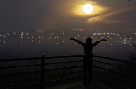 meditaion: Silhouette back of girl raising two arm embracing to moon at night with blurred bokeh highland city top view