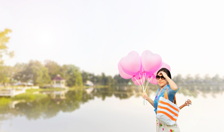 cary: Asian women wearing sunglasses with ukulele in summer bag carried on the shoulder taking heart shape pink balloons in hand with lake public park view background