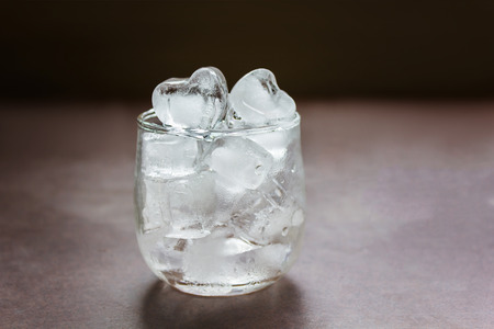 stillife: Still-life heart shape plain ice water in glass on table with dim light and copy space Stock Photo