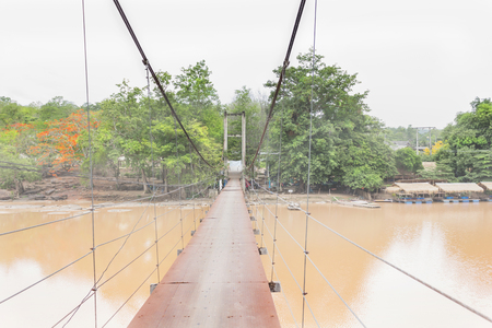 folk village: long rope bridge across the river in village at Thailand countryside, folk way across waterfall, Kheck River with trees at riverside view