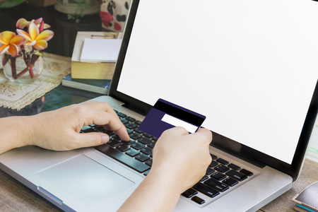swiftly: Women hands hold credit or debit card (ATM) and notebook or laptop for internet working, online buying and shopping, blank screen laptop, empty screen computer
