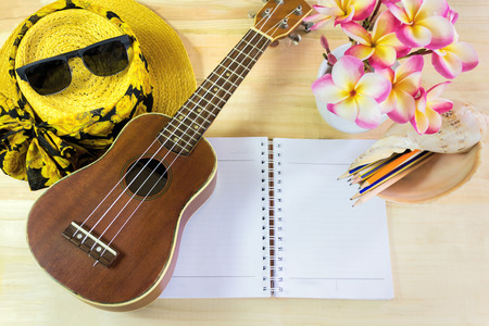 copy sapce: Ukulele and pink yellow and white flowers bunch plumeria or frangipani with background of lady summer hat and sunglasses on wooden table, fresh summer mood with blank note book area for text , summer background with copy sapce