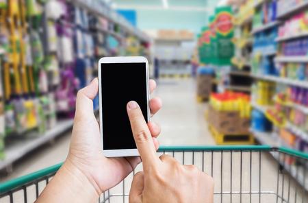 Hand press on big blank smartphone screen or mobile phone on shopping mall background, blank cellphone screen and hands in supermarket background Standard-Bild