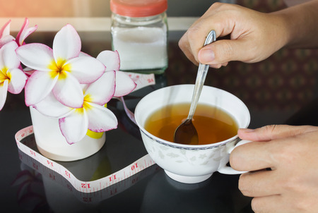 measures: Hands with cup of tea and background of tape measures and sugar, diet or weight loss tea, cup of laxative tea and girl or women hand Stock Photo