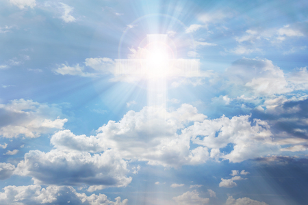Light from sky or heaven shine trough soft crucifix or cross form on pure white shining puffy clouds sky