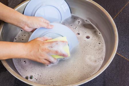 lavar platos: manos lavar los platos, las manos con la almohadilla scrubbibg o almohadilla de esponja y de la burbuja de líquido para lavar platos con platos y agua en la cuenca, esponja exfoliante (lavavajillas)