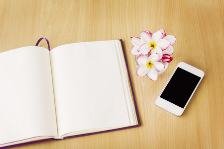 memorandum: Smartphone and blank note book or diary in relax mood, empty note book or diary with frangipani or plumeria on work table, blank page diary memorandum and smartphone Stock Photo