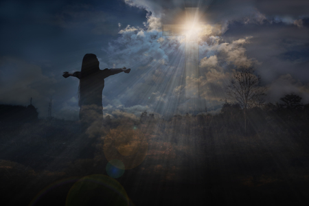 Back or rare of women with crucifix or cross form and light from dark sky, God light expel darkness