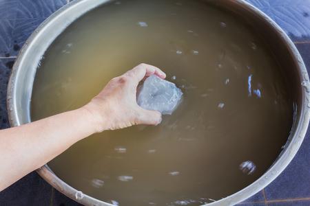 crystalline: Hand dip alum in muddy water to precipitate muddy water clear, alum turn muddy water to crystalline, hand soak alum to turbid water, settle muddy water by alum