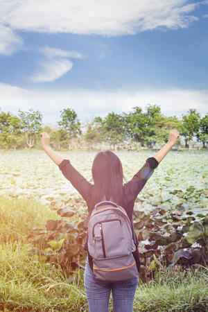 packsack: Women back or rare view with focused backpack on natural pond and puffy clouds sky view, women raise or stetch two arms ,relax at the pond