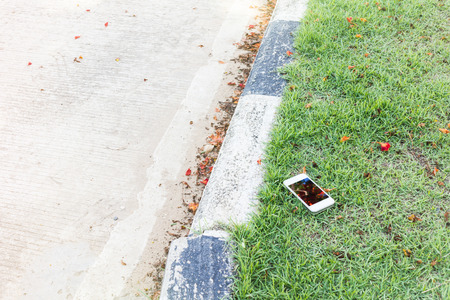 belongings: Smartphone on grass field beside the road,drop or loss  smartphone or cellphone or mobile phone on street,missing and loss belongings concept