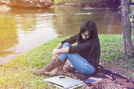 waiting phone call: Girl sitting on grass field at riverside with laptop and smartphone, girl or women looking at smartphone or waiting phone call in relax mood among natural river view background