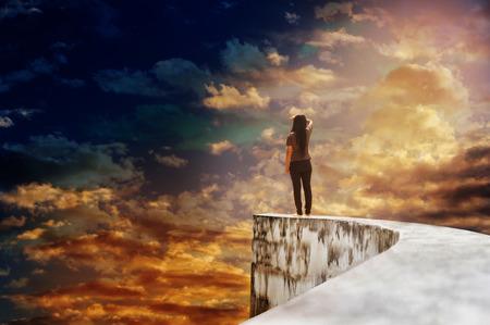 Backside of zeldzame weergave van de vrouw of meisje op doodlopende hoge manier voetpad of de bovenkant van de muur op mysterie bewolkte grote en uitgebreide hemel met dromerige en fancy stemming, vrouwen kijk naar de hele wereld