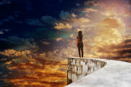 Backside or rare view of women or girl on dead end high way footpath or top of wall on mystery cloudy vast and extensive sky with dreamy and fancy mood, women look up at worldwide
