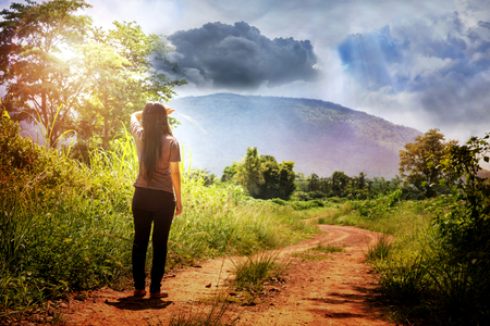 girl looking up: Back or rare view of girl or women standing on non-asphalt road looking up to wierd big clouds sky
