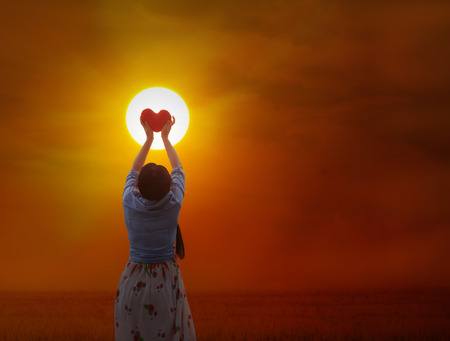 gently: Back or rare view of women gently hold red heart with love, care and restpect to the sun on grass field and sunset twilight background
