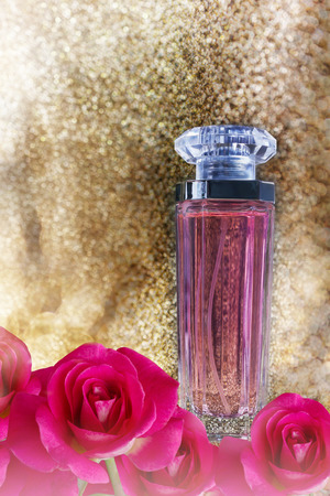 parfume: Single fragrant perfume or au de parfume with pink roses flowers on golden glitering shine sparkle luxury bokeh dreamy background