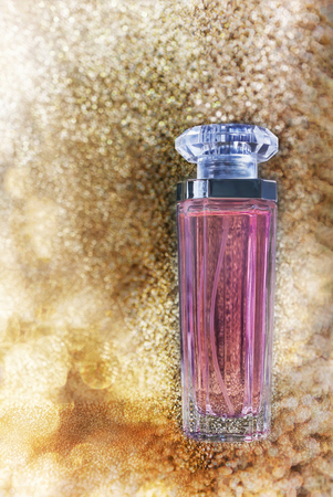 parfume: Single fragrant perfume or au de parfume on golden glitering shine sparkle luxury bokeh dreamy background