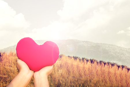 invigorate: Two hands gently raise and hold big red heart with love and respect with background of nature in vintage brown colour tone  for valentine or take care with love concept idea Stock Photo