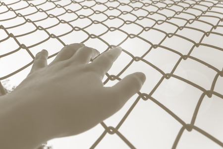 imprison: Hand catching iron bar with imprison feeling, freedom desire concept Stock Photo