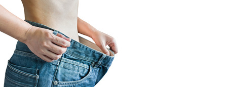 changed: Isolated closeup loose denim jeans trouser at waist, diet girl or women and slender or body changed for beauty and healthy concept Stock Photo