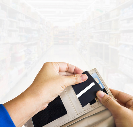 pull out: Hands pull credit or debit card (ATM) out of wallet with blurred supermarket background