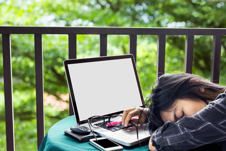 drowsy: Women have a wink or drowsy at notebook,women tired or exhausted and doze off on table with laptop or computer at balcony with blurred tree background