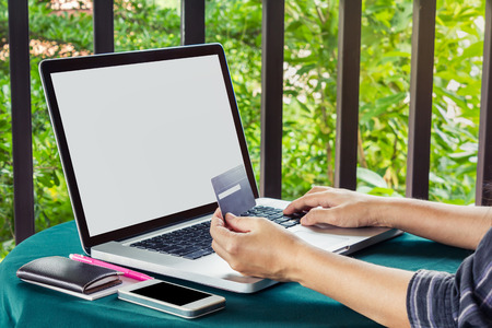 swiftly: Hands hold credit or debit card infront of notebook for internet working or online shopping
