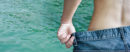 undress: Back or rare of women undress denim jeans on sea or crystalline water surface background with blank space area Stock Photo