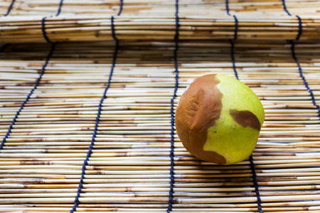 decompose: Spoil or putrefy apple on mat