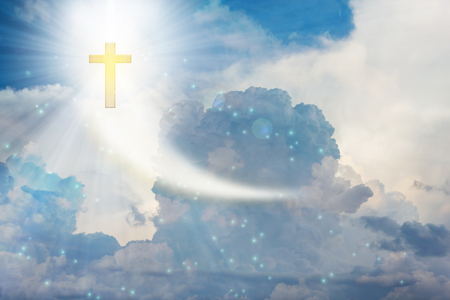Crucifix or cross on heaven cloudy sky with lens flare Stock Photo