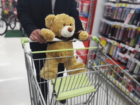 departmentstore: Cute brown bear catching shopping cart with man with background of departmentstore