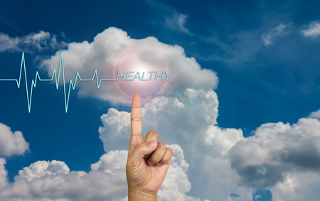 healthier: Pulse or heart beat and text healthy with hand on sky Stock Photo