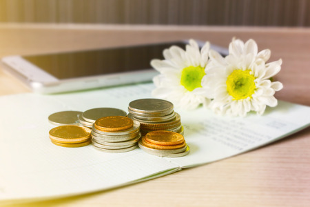 Coins on book bank account for money saving concept