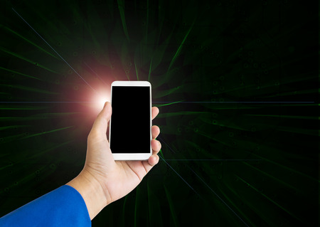 technolgy: Hand hold smart phone or moblie phone on modern light and lens flare on electronic technolgy dark background Stock Photo