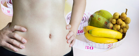 Close up waist and fit belly on tape measure wire background , diet for healthy and beauty or weight loss diet concept