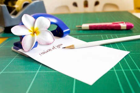 Text I think of you on note pad or memo pad with plumeria or frangipani flower on working table in office