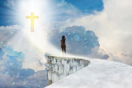 Crucifijo o una cruz en el cielo nublado cielo con reflejo en la lente y la parte trasera o rara vista de la mujer o niña en punto muerto sendero de forma alta o la parte superior de la pared Foto de archivo