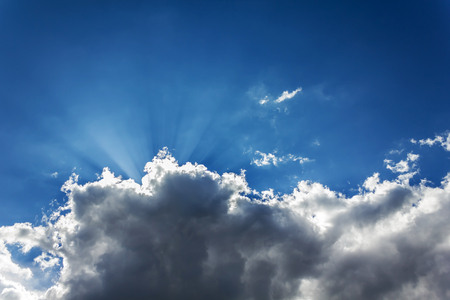 Sun ray light emerge or spread trought the big dark cound on blue wide sky