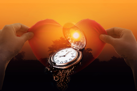 Clock or watch on shadow of hand catch red heart with silhouette or shadow of tree in sunset  twilight background Stock Photo