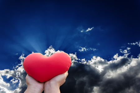 Hand gently hold red heart with love, careness and restpect on dark blue sky with clouds and sun ray background