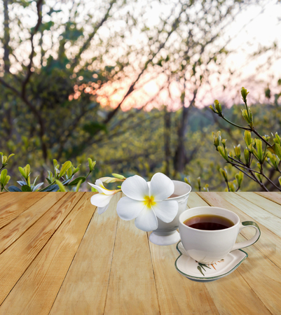 Classic white cup of black coffee decorated with flower on green nature background for concept afternoon coffee in simply style and relax time